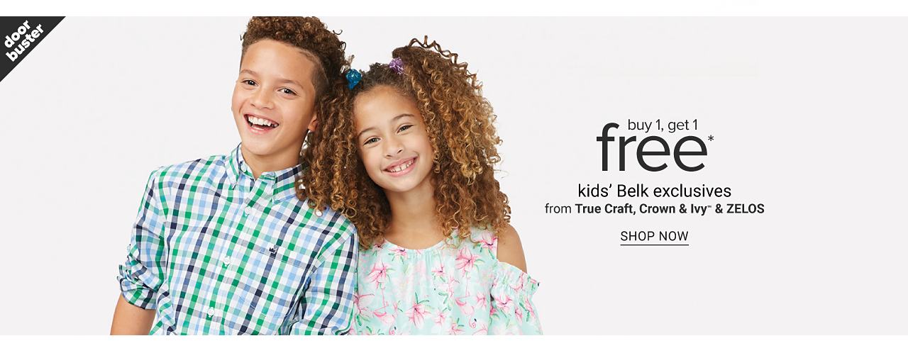 A boy wearing a white, blue & green plaid long sleeved button front shirt standing next to a girl wearing a multi colored floral print short sleeved dress. Doorbuster. Buy 1, Get 1 Free kids Belk exclusives from True Craft, Crown & Ivy & Zelos. Shop now.
