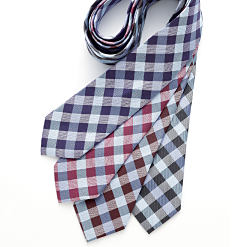 An assorted of plaid patterned ties in a variety of colors. Shop ties.