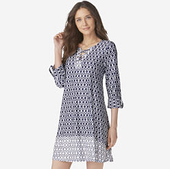 A woman wearing a navy & white patterned long sleeved dresses. Shop dresses.