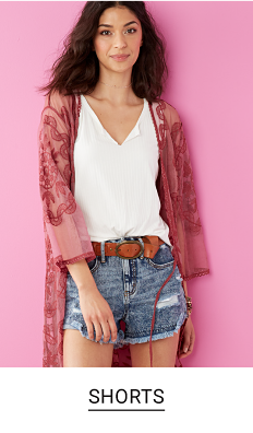 A young woman in a magenta cover-up, white v-neck tee shirt, brown belt and blue denim shorts. Shop shorts.