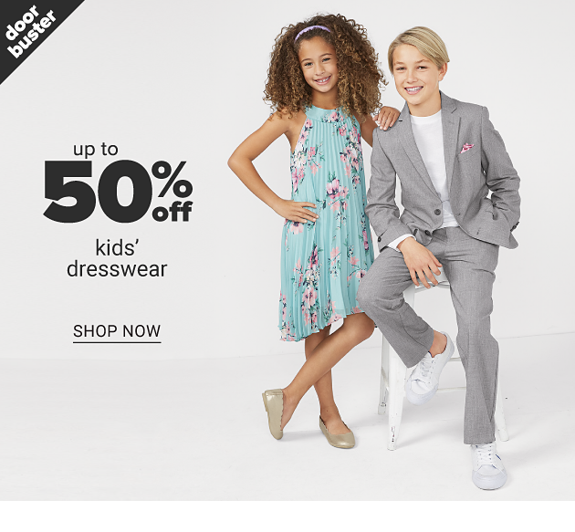 A girl wearing a multi colored floral print sleeveless dress & silver flats standing next to a boy wearing a light gray suit, white shirt & white sneakers. Doorbuster. Up to 50% off kids dresswear. Shop now.