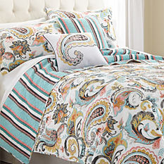A bed made with a multi-colored print quilt & matching pillows. Shop quilts.