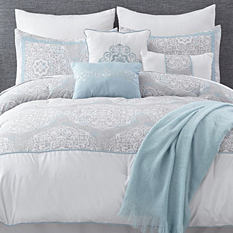 A bed made with a white & gray patterned comforter & matching pillows. Shop bed in a bag.