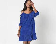A woman wearing a blue cold shoulder dress. Shop dresses.
