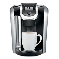 A Keurig coffee maker & a white mug. Shop coffee makers.