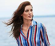 A woman wearing a multi-colored vertical striped long sleeved button front blouse. Shop Lauren Ralph Lauren.