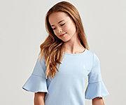 A girl wearing a light blue short sleeved top. Shop Polo Ralph Lauren Kids.