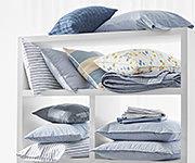 An assortment of pillows on shelves. Shop Lauren Home.