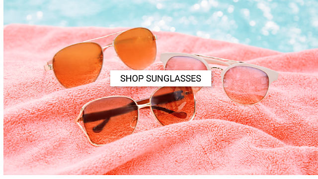 An assortment of sunglasses in a variety of styles on a coral beach towel. Shop sunglasses.