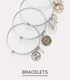 An assortment of bracelets in silver and gold with a variety of charms. Shop bracelets.
