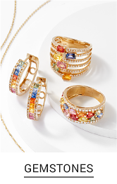 An assortment of gold jewelry with gems in a variety of colors. Shop gemstones.
