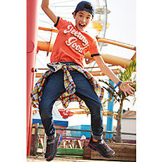 A boy wearing a navy backwards baseball cap, an orange, white & black Feeling Good graphic T shirt, blue jeans & plaid flannel shirt tied around his waist & dark gray sneakers. Shop boys.