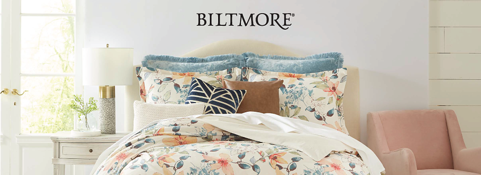 A bed made up in a floral themed comforter with matching pillows. Biltmore.