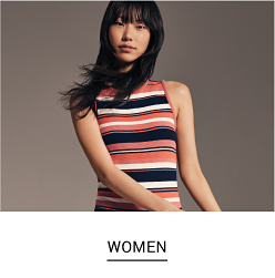 A woman in a navy, white, and orange sleeveless top. Shop women.