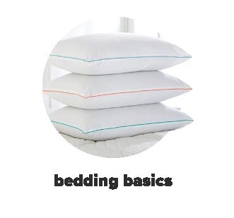 Three pillows stacked on mattress topper. Shop bedding basics.