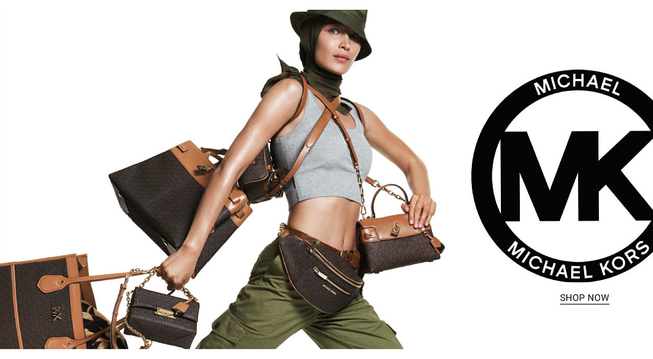 A woman wearing an olive green bucket hat, a black head scarf, a gray sports bra & olive green pants, carrying several different styles of handbags. Michael Michael Kors. Shop now.