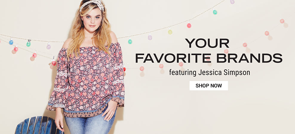 A woman wearing a multi-colored print cold shoulder peasant top & blue jeans. Your Favorite Brands featuring Jessica Simpson. Shop now.
