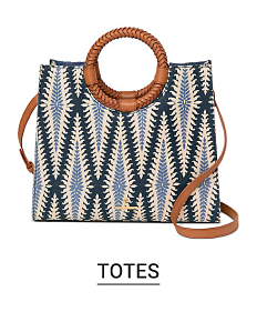 A cross stitch design navy blue, light blue and white tote with a round handle and crossbody strap. Shop totes.