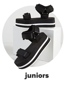 A pair of black platform sandals featuring a white horizontal stripe along the sole. Juniors.