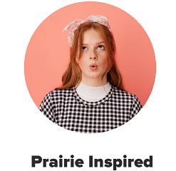 A woman with a pink bow in her hair, a white turtleneck and a black and white gingham top. Prairie inspired.