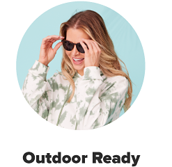 A woman in black sunglasses with a white and green tie dyed hoodie. Outdoor ready.