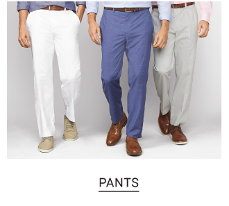 A man in white dress pants and beige shoes. A man in blue pants and brown dress shoes. A man in light khaki pants and brown dress shoes. Shop pants.