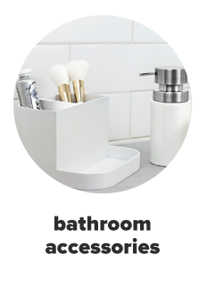 A white bathroom organizer with toothpaste on one side and two white makeup brushes on the other side. A silver and white soap dispenser. Bathroom accessories.
