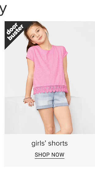 A girl in a hot pink tee shirt with a lacy hem line and denim shorts. Doorbuster. Girls shorts. Shop now.
