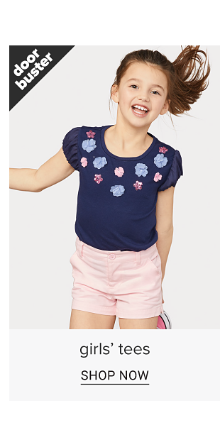 A girl in a navy blue peasant style tee shirt with pink and purple floral designs and in pink shorts. Doorbuster. Girls tees. Shop now.