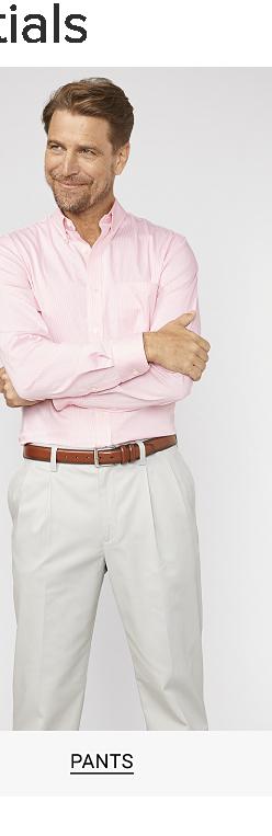 A man in a pink button down shirt, brown belt and khaki pants. Shop pants.
