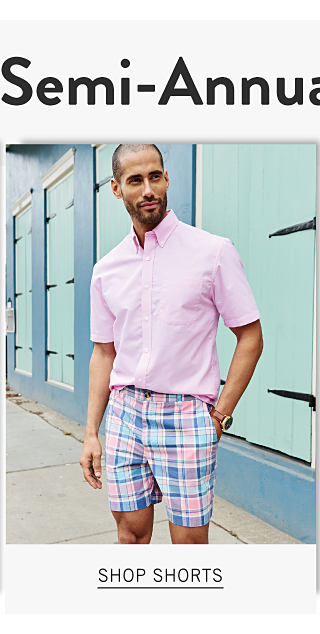 A man wearing a pink short sleeved button front shirt & blue & white plaid shorts. Shop shorts.