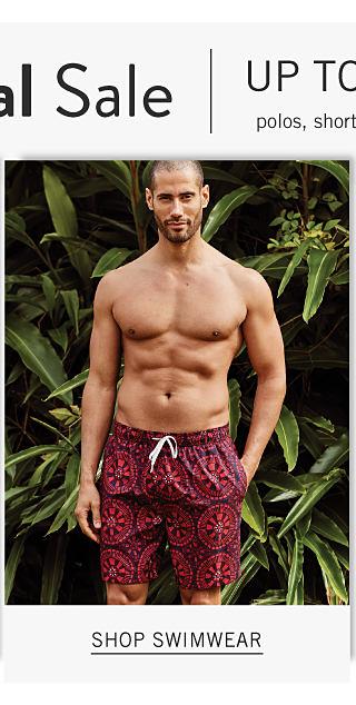A man wearing red & black patterned print swim trunks. Shop swimwear.