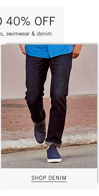 A man wearing a blue short sleeved button front shirt with white dots, blue jeans & navy sneakers. Shop denim.