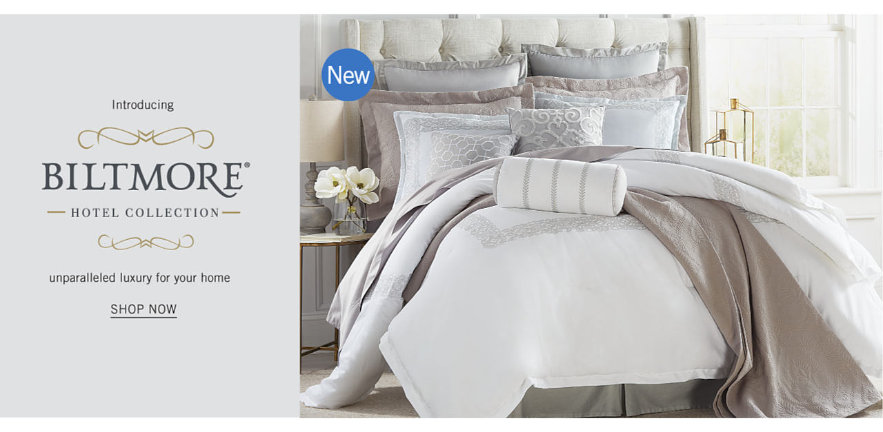 A bed made with a white comforter with a gray print, a gray quilt & an assortment of white & gray pillows. New. Introducing Biltmore Hotel Collection. Unparalleled luxury for your home. Shop now.