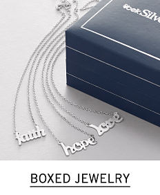 An assortment of silver tone asirational necklaces next to a blue jewelry box. Shop boxed jewelry.