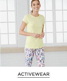 A woman wearing a yellow short sleeved top & multi colored floral print pants. Shop activewear.