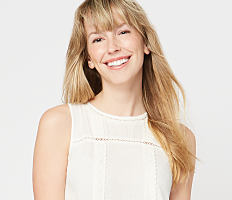 A young woman wearing a white sleeveless dress. Shop juniors.