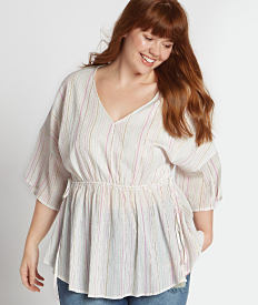 A young woman in a three quarter sleeve, white peasant top with light pink vertical stripes. Shop tops.
