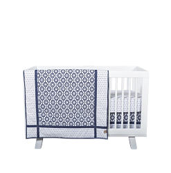 A navy & white patterned print blanket draped over the side of a white crib. Shop Nursery & Decor.