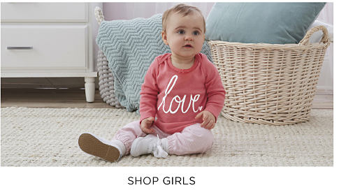 A baby girl wearing a coral & white long sleeved top, pink pants & pink sneakers. Shop girls.