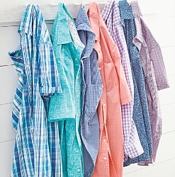 An assortment of men's button front shirts hanging from hooks on a wall. Shop big & tall,