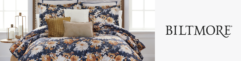 A navy blue comforter set with an orange and off-white flower design with matching pillowcases. An off-white pillow, a mustard colored pillow and a rectangular beige pillow. Biltmore.