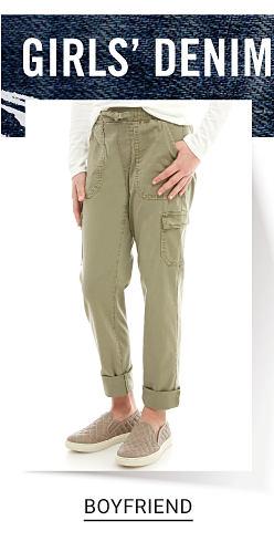 Girls Denim. A girl wearing a white long sleeved top, beige cargo pants & beige sneakers. Shop boyfriend.