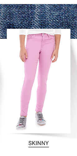 A girl wearing a white long sleeved button front blouse, pink jeans & pink sneakers. Shop skinny.