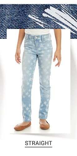 A girl wearing a white T shirt, light blue jeans with all over white star patterned print & brown flats. Shop straight.