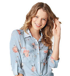 A young woman wearing a denim blue blosue with a rose patterned print. Shop tops.