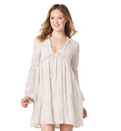 A young woman wearing a white long sleeved dress. Shop dresses.