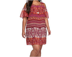 A young woman wearing a multi colored patterned print short sleeved dress. Shop dresses.