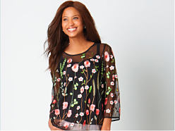 A woman wearing a multi colored floral print long sleeved top. Shop Rafaella.
