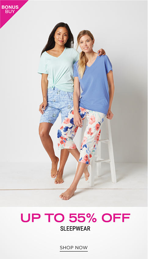 A woman wearing a mint green tee & blue & white sleep shorts standing next to a woman wearing a light blue tee & multi colored floral print pajama bottoms. Bonus Buy. Up to 55% off sleepwear. Shop now.